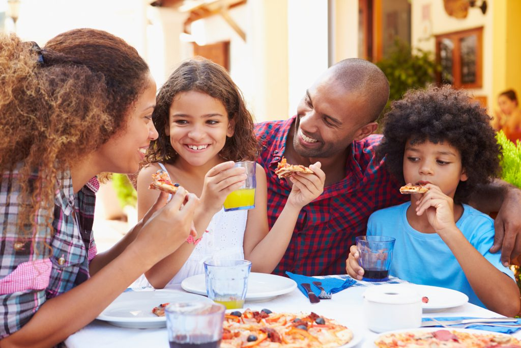 Family Eating Meal At Outdoor Restaurant Together, Smiling, woman eating a piece of pizza, girl eating a slice of pizza and drinking orange juice, man smiling and boy eating pizza