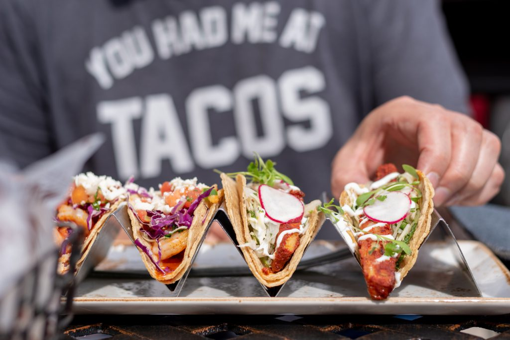 closeup of man eating tacos in summer with a shirt that says you had me at tacos in the background