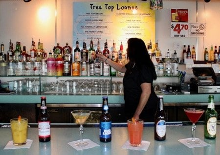 A bartender reaching for a bottle while drinks are displayed in front of her.