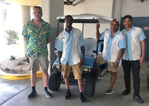 Four bellman standing in front of a golf cart