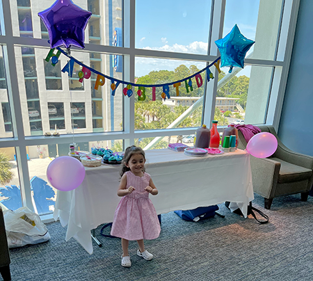 small child wearing a dress with two star balloons and a happy birthday banner in the background