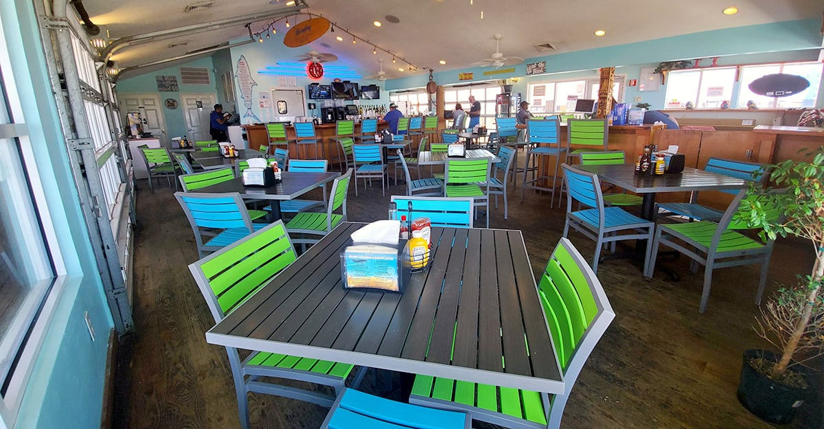 A tropical beach cafe with brightly colored chairs and tables.