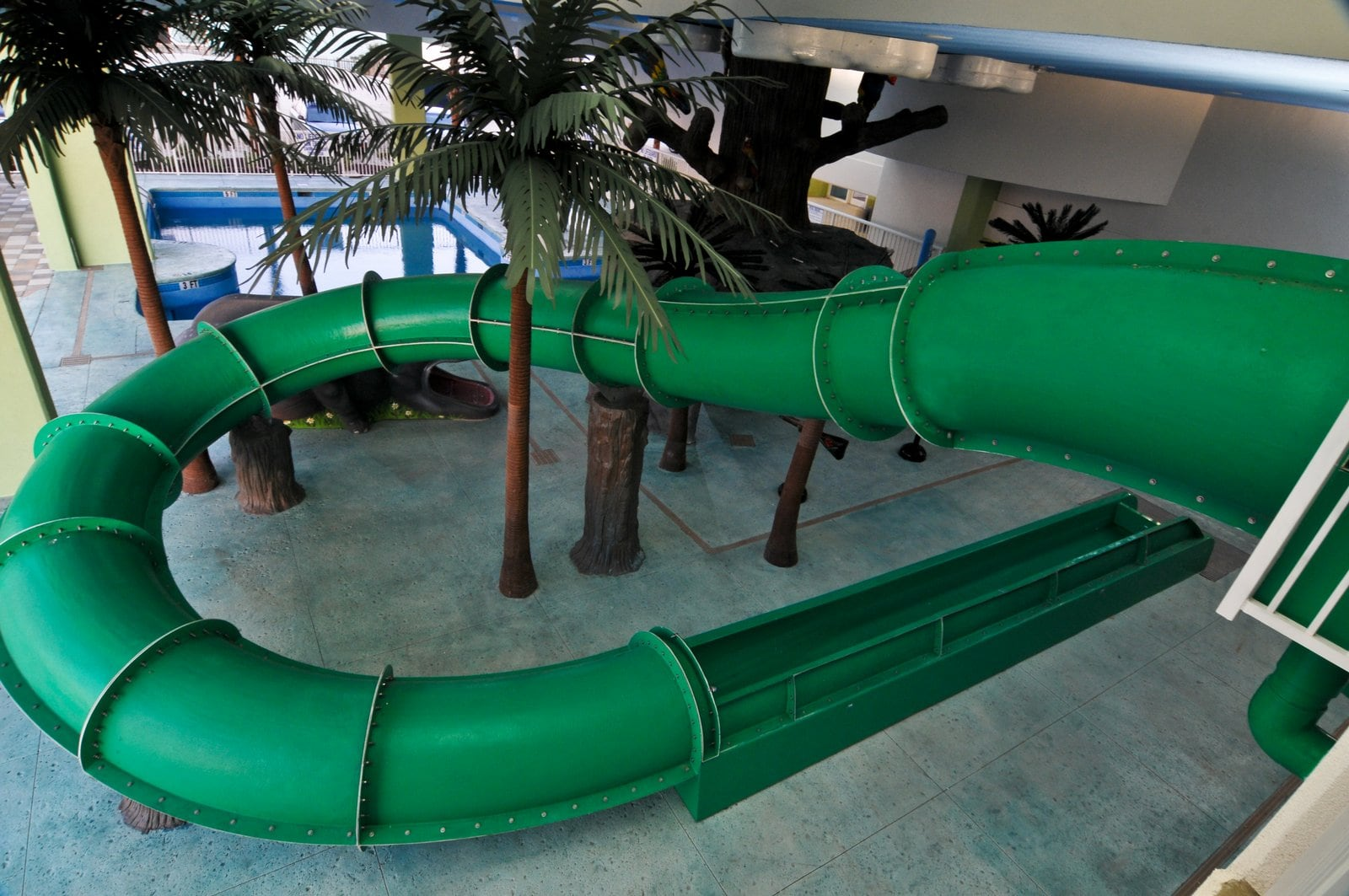 The outside of a long twisted green water slide